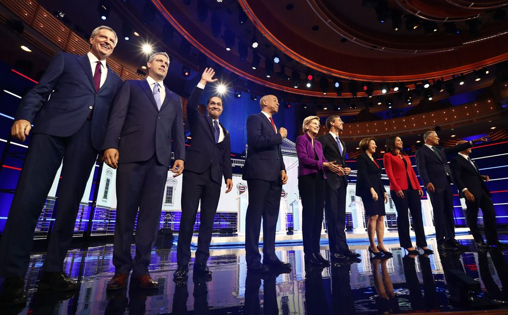 From left, New York City Mayor Bill de Blasio, Rep. Tim Ryan, D-Ohio, former Housing and Urban Development Secretary Julian Castro, Sen. Cory Booker, D-N.J., Sen. Elizabeth Warren, D-Mass., former Texas Rep. Beto O'Rourke, Sen. Amy Klobuchar, D-Minn., Rep. Tulsi Gabbard, D-Hawaii, Washington Gov. Jay Inslee, and former Maryland Rep. John Delaney pose for a photo on stage before the start of a Democratic primary debate hosted by NBC News at the Adrienne Arsht Center for the Performing Arts, Wednesday, June 26, 2019, in Miami. (AP Photo/Brynn Anderson)