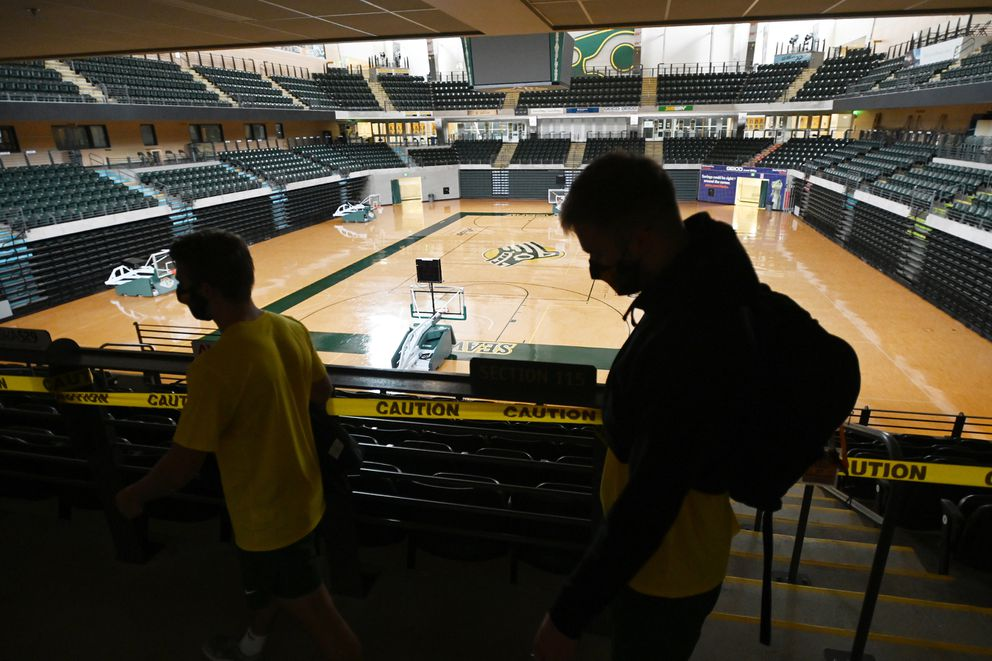 UAA men's basketball players Caleb Larsen, left, and Keegan Crosby are silhouetted as they leave the Alaska Airlines Center after a workout. (Bill Roth / ADN)