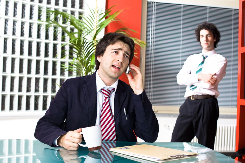 Successful business manager and envious employee at office. (Getty)