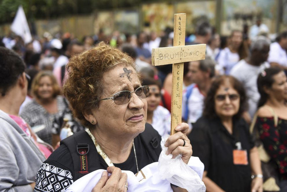 A woman holds a cross during a tribute to those who died in the dam disaster last year in Brumadinho city, Minas Gerais state, Brazil, Saturday. (AP Photo/Gustavo Andrade)