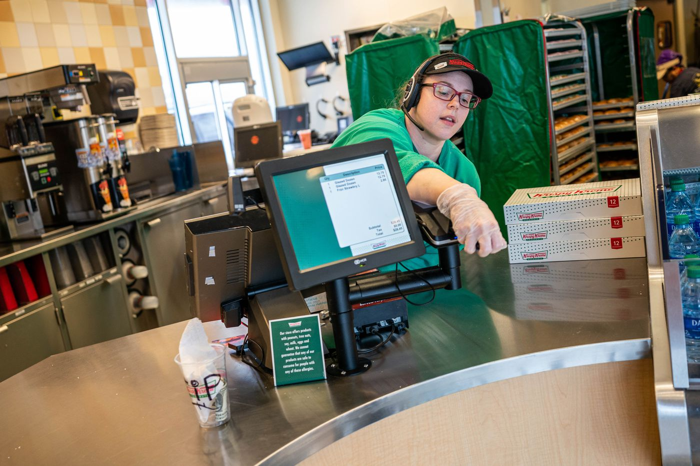 """Amber Starks processes a credit card payment for a drive-through customer at Krispy Kreme on Wednesday, March 18, 2020 in Anchorage. The business has modified its operations since the coronavirus outbreak, letting some staff go. """"I'm just happy to still have a job,"""" said Starks, a single mother of two children. (Loren Holmes / ADN)"""
