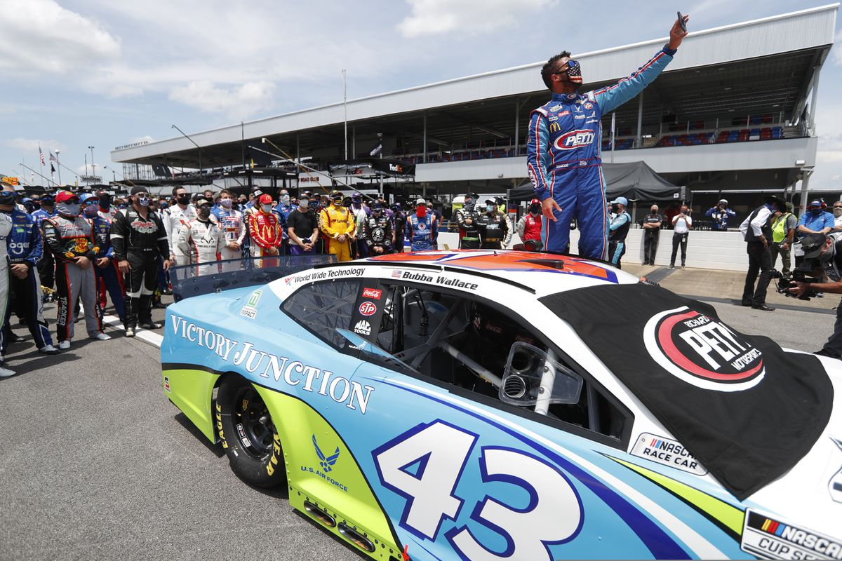 Driver Bubba Wallace takes a selfie with himself and other drivers who pushed his car to the front in the pits of the Talladega Superspeedway prior to the start of the NASCAR Cup Series auto race at the Talladega Superspeedway in Talladega Ala., Monday June 22, 2020. (AP Photo/John Bazemore)