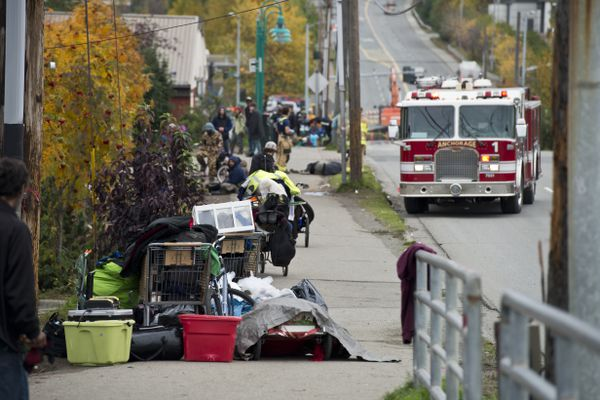 Belongings are piled up along Third Avenue during a cleanup of the area. Members of the Anchorage Police Department direct a cleanup along Third Avenue and Barrow Street where many homeless people had been staying on Sept. 27, 2017. (Marc Lester / Alaska Dispatch News)