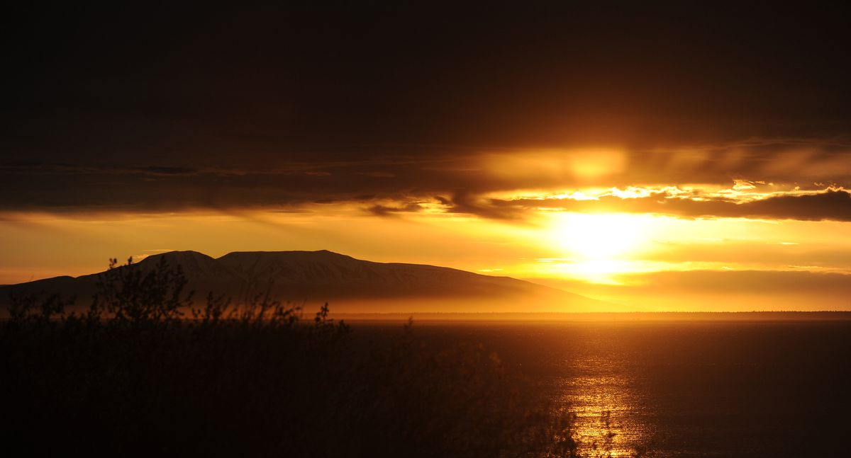 The sun sets next to Mount Susitna across Cook Inlet from Anchorage. (Bob Hallinen / ADN)