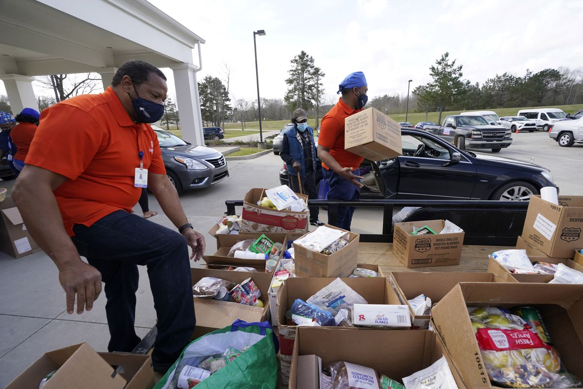 Mississippi SHINE Project team members distribute boxes loaded with a variety of staples, dried foods, powered milk, small blocks of cheese, canned vegetables, dried beans and apples to residents at the Jefferson Comprehensive Health Center in Fayette, Miss., on Friday, March 12, 2021. (AP Photo/Rogelio V. Solis)