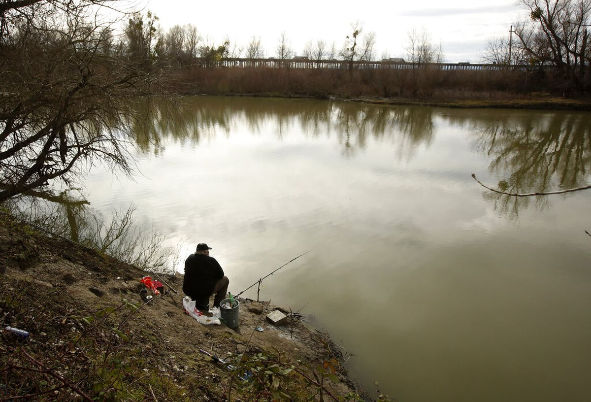 A fisherman sits along the slough, Monday Jan. 27, 2020, where the body of an infant, Nikko Lee Perez, was discovered in Yolo County in 2007, near Woodland, Calif. Paul Perez, a California father about to be freed from prison, has been taken into custody in connection with the decades-old killings of five of his infant children including Nikko in a case a sheriff said has haunted his agency for years. He was charged in the deaths of the children born between 1992 and 2001, authorities announced Monday. (AP Photo/Rich Pedroncelli)