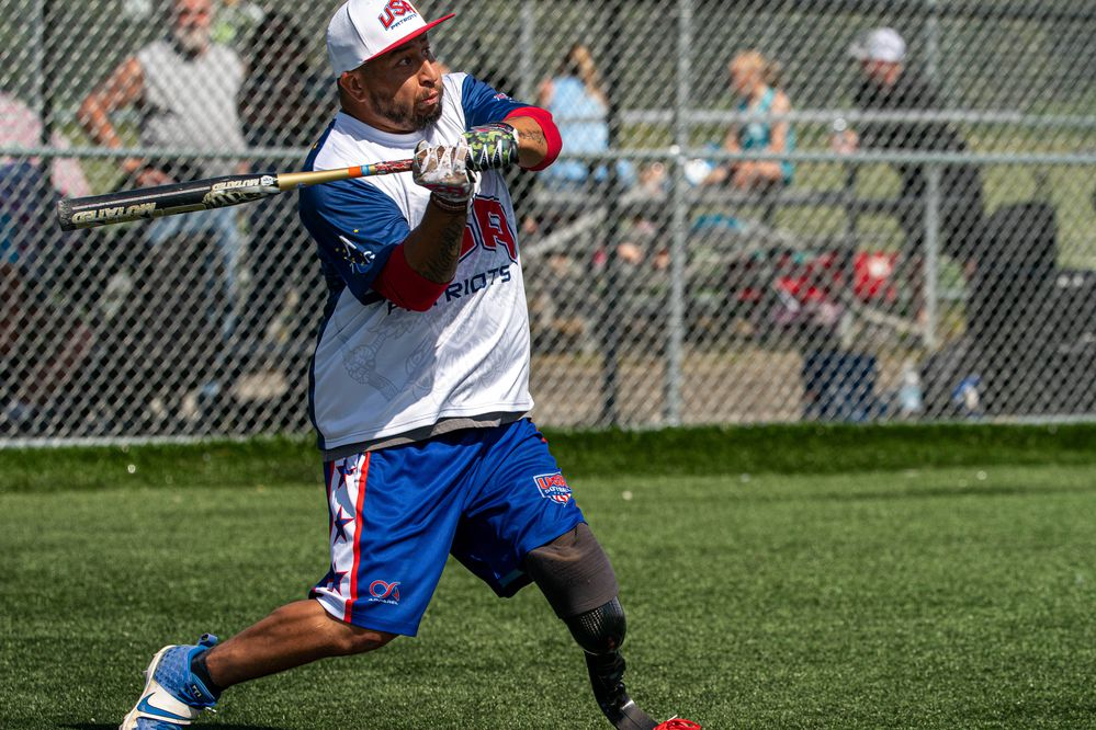 USA Patriots team member Saul Monroy hits the ball during a softball game at the 2021 Pot of Gold Tournament on Saturday, June 12, 2021 at Cartee Fields in Anchorage. Monroy was deployed to Afghanistan in 2010 with the Marines when his vehicle was struck with an improvised explosive device, leaving him with injuries requiring the amputation of his left leg. (Loren Holmes / ADN)