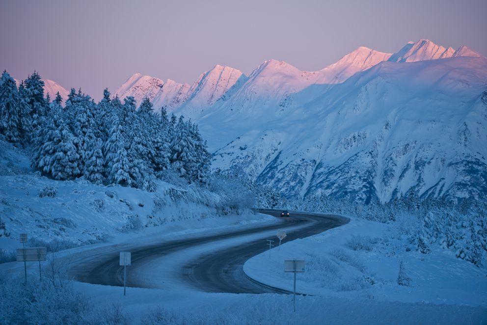 Peaks near Turnagain Pass catch the last bit of afternoon sunlight as a car heads southbound on the Seward Highway on Thursday, December 22, 2016. (Marc Lester / Alaska Dispatch News)