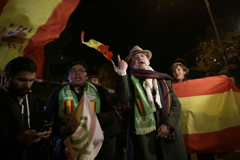 Spain's far-right Vox party supporters wave Spanish flags while waiting for the announcement of the general election results, in Madrid, Spain, Sunday, Nov. 10, 2019. Spain's Interior Ministry says that early results show Socialists winning Spain's national election, but without a clear end to the country's political deadlock. Vox is also surging to become the country's third political force, preliminary data with 22% votes counted show. (AP Photo/Andrea Comas)