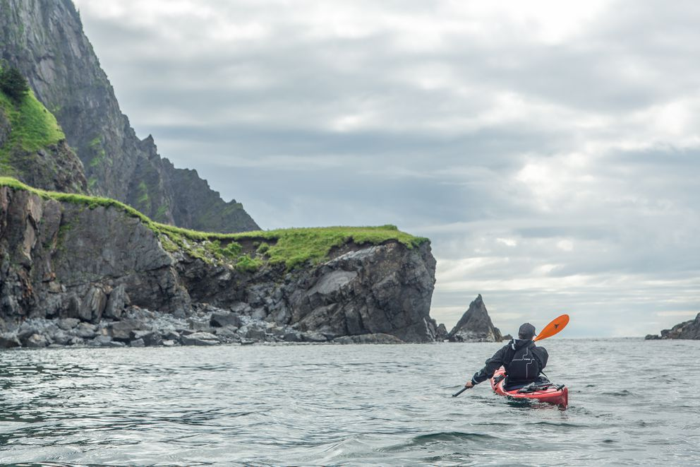 Kim McNett paddles in front of Gore Point in the Kenai Fjords. Bjørn and Kim spent three-weeks in 2016 sea kayaking from their home in Homer to Seward where they met friends, then fat-biked and packrafted back home. (Bjørn Olson)