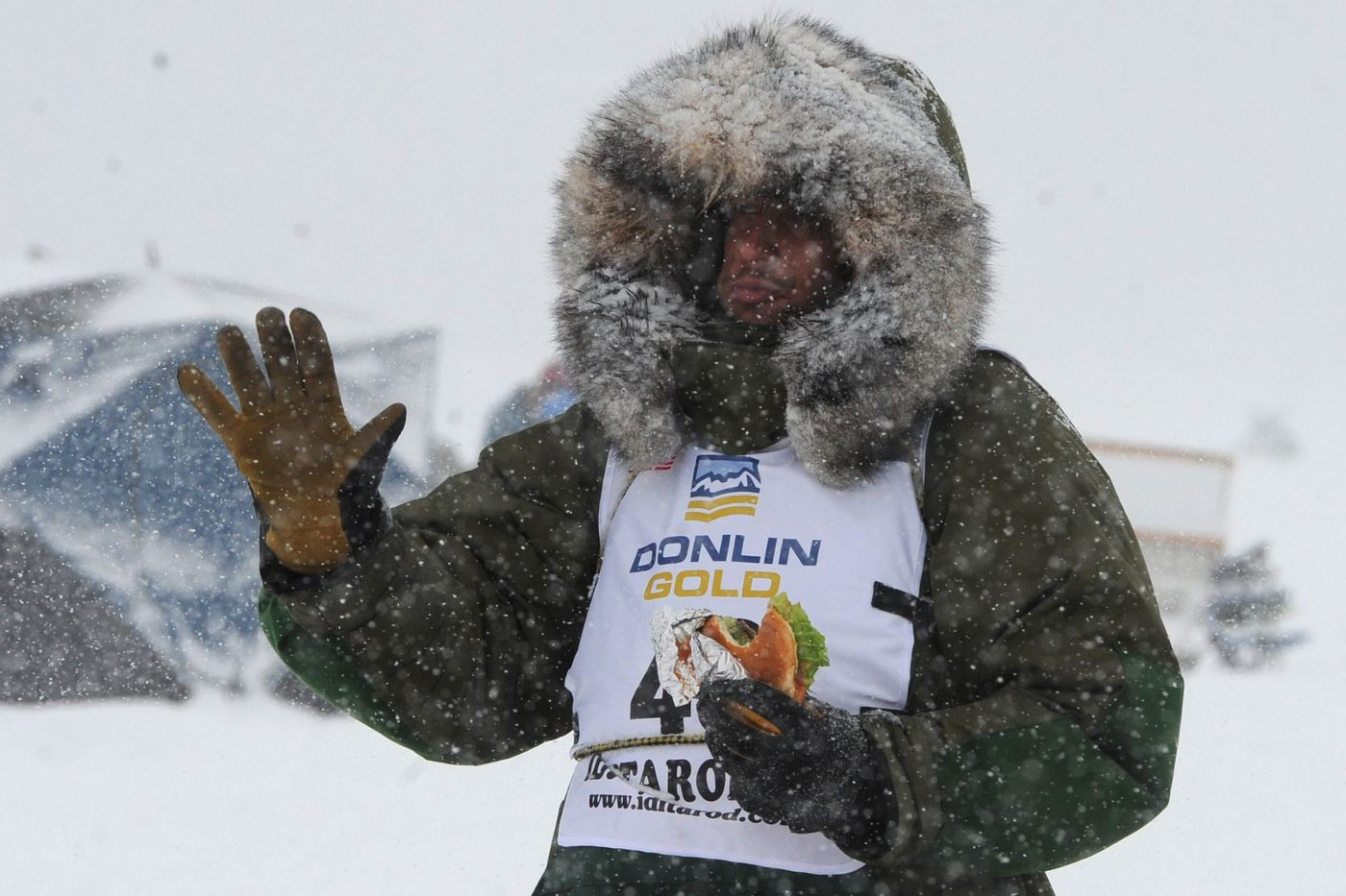 Iditarod rookie Sean Underwood eats a sandwich while driving Jeff King's dog team across Long Lake during the restart of the Iditarod. (Bill Roth / ADN)