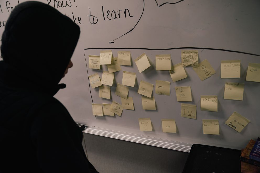 Fifth-graders from Ponderosa Elementary School leave sticky notes describing how they feel on a board at Durham Elementary, where they have attended classes since the wildfire. The resumption of school brought emotional reunions for students and teachers. (Photo by Mason Trinca for The Washington Post)