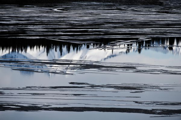 Chugach Mountain peaks reflect in a pond along the Glenn Highway in Glacier View on May 15, 2020. (Marc Lester / ADN)