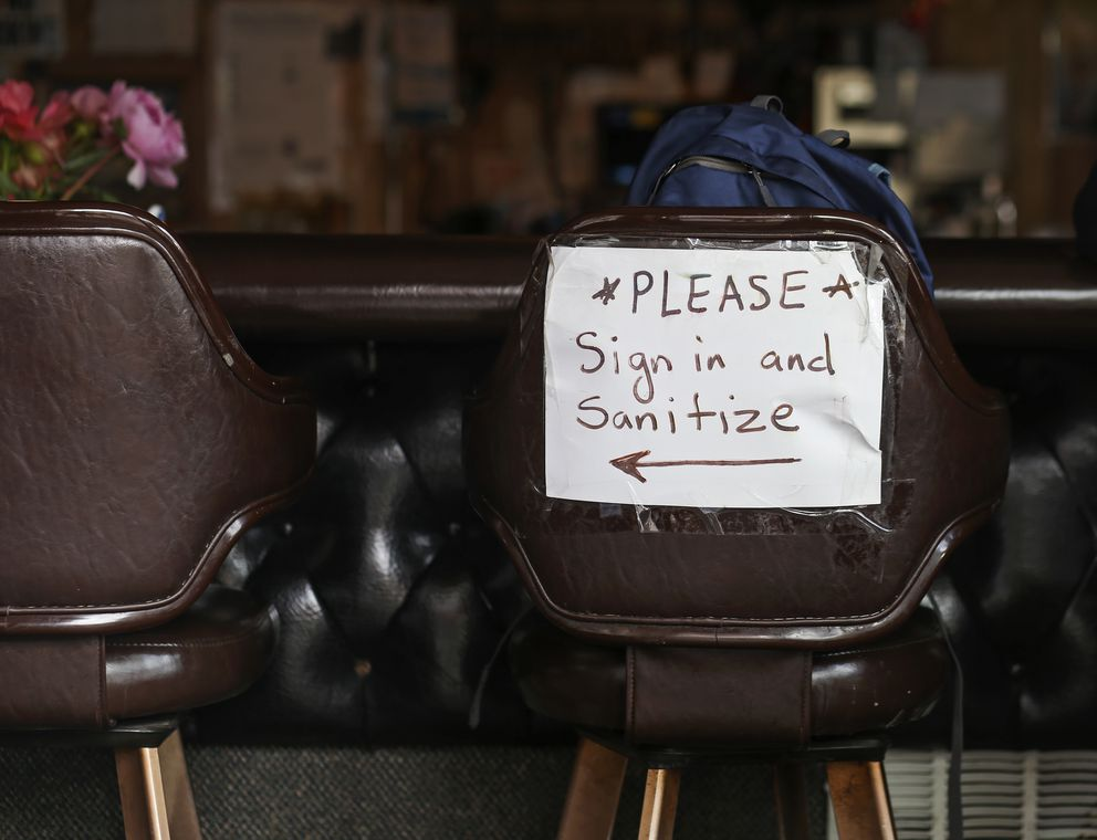A sign directing customers to a sign-in and sanitizing station is taped to the back of a bar stool at Darwin's Theory in Anchorage on July 31, 2020. (Emily Mesner / ADN)