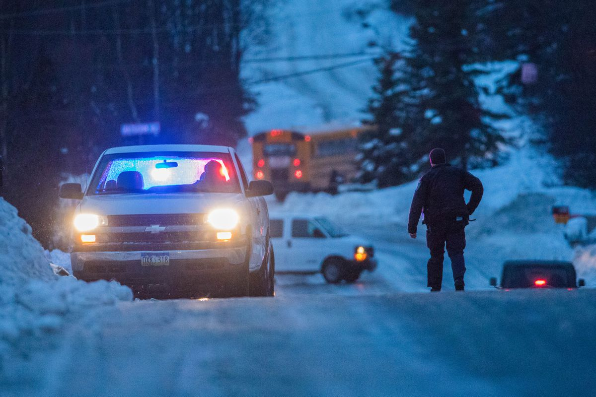 A police officer helps motorists stranded on the side of an icy Hillside Drive early on Jan. 26, 2017. Freezing rain made roads extremely icy during the morning commute. (Loren Holmes / ADN archive)
