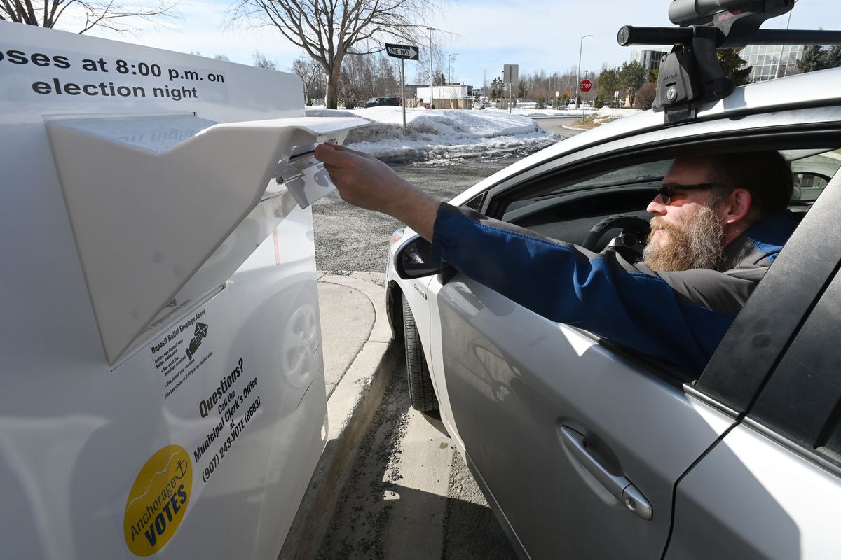 Bryan Talbott-Clark places a ballot in a secure vote-by-mail ballot drop box at the Loussac Library on April 6, 2020. (Bill Roth / ADN archive)