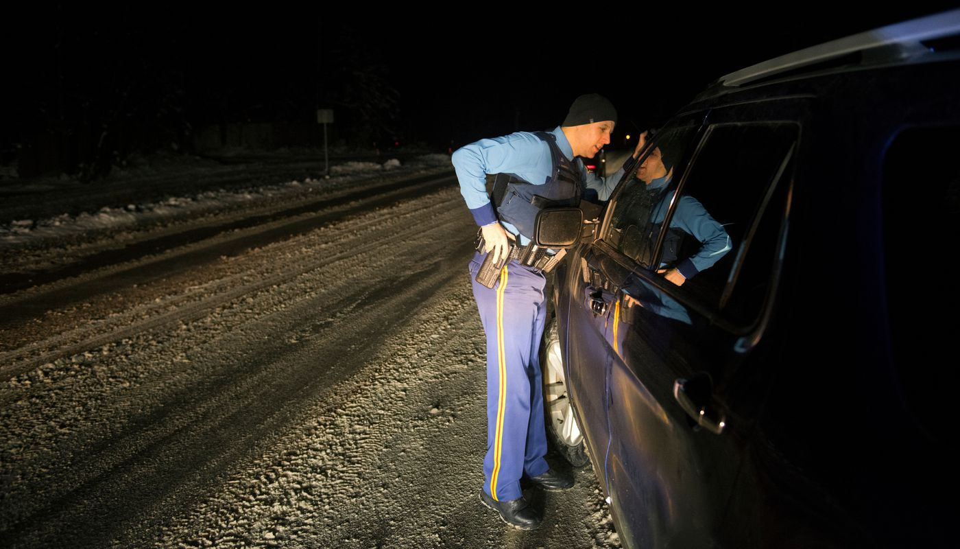 Alaska State Trooper Ryan Anderson looks into a vehicle with a broken window that was left on the shoulder of a Wasilla road on November 18, 2019. (Marc Lester / ADN)