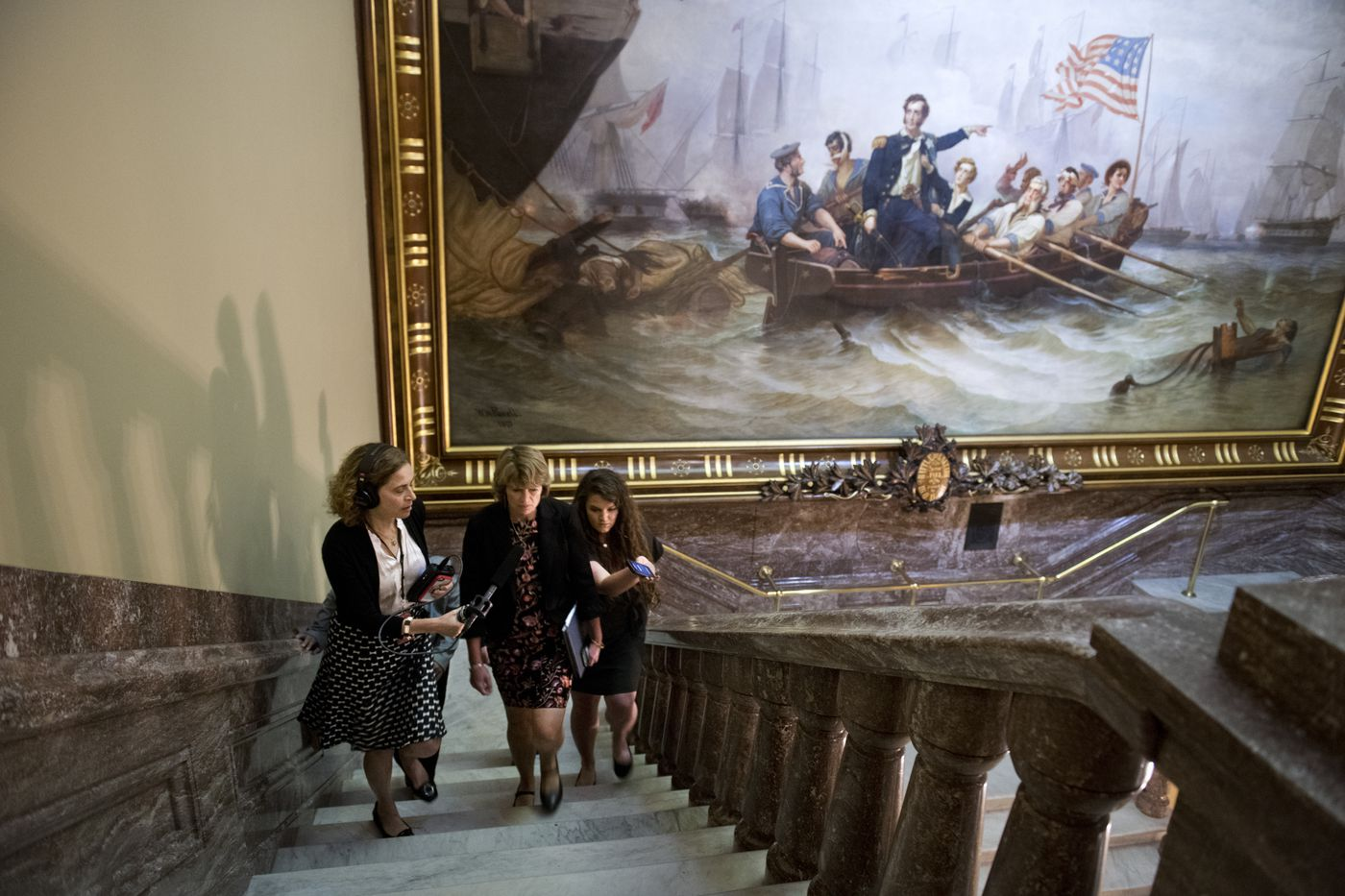 Sen. Lisa Murkowski, center, answers questions from Alaska public radio reporter Liz Ruskin, left, in a Capitol stairwell on June 18, 2019. Murkowski's press secretary Hannah Ray is at right. (Marc Lester / ADN)