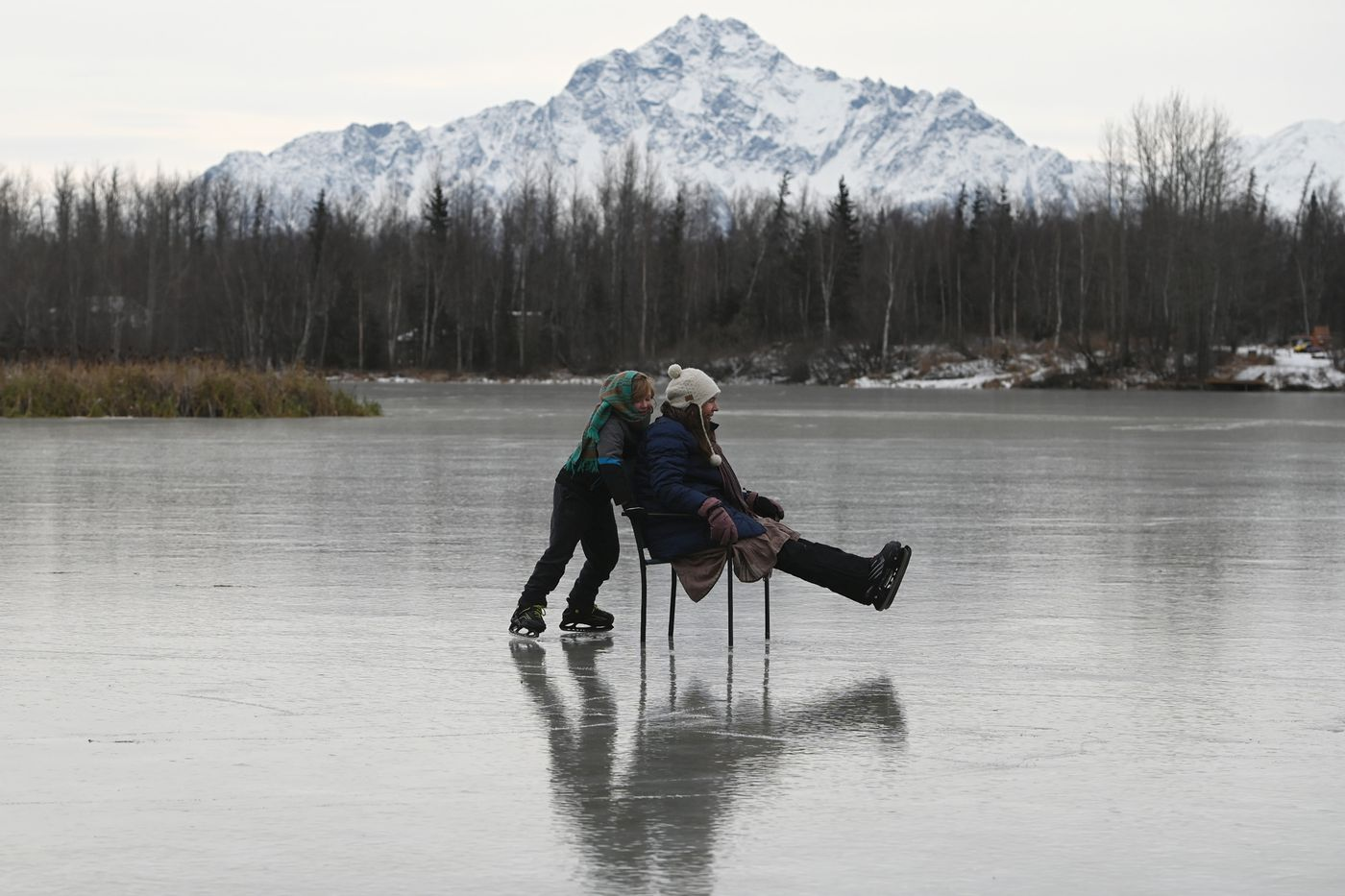 Ezra Gately, 7, pushes his mother Kara Sterling in a chair as they went ice skating for the first time this season at Finger Lake on Thursday, Nov. 5, 2020. Pioneer Peak is in the distance as clouds began to move in with snow in the forecast. (Bill Roth / ADN)