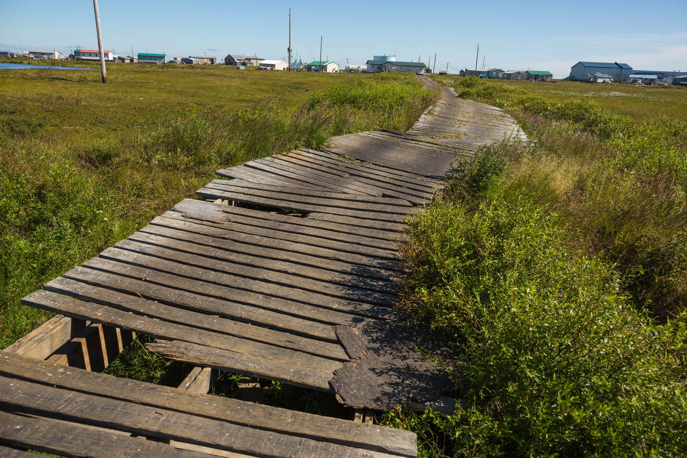 The boardwalk leading from the Newtok airport to the clinic, on Tuesday, August 4, 2015. With efforts underway to move the village to a new site, the existing infrastructure has been neglected.
