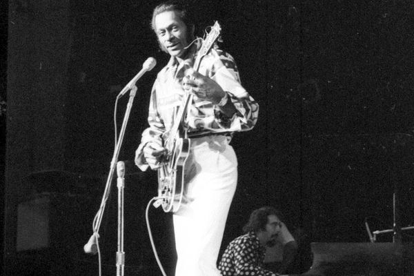 Chuck Berry plays the stage at West High School in October 1974. Mr. Whitekeys is on the keyboard in the background. (Steven Denenberg)