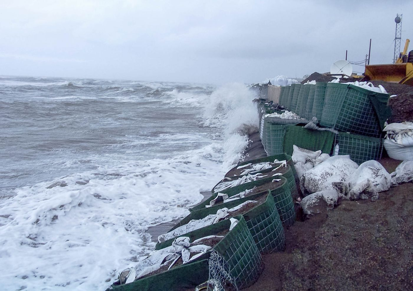 Waves pound against the sandbagged seawall in Kivalina, Alaska on September 13, 2007. A storm surge and pounding waves sheared off large segments of Kivalina's multimillion dollar sea wall causing more than 200 residents to evacuate the village built on a slender strip of land.
