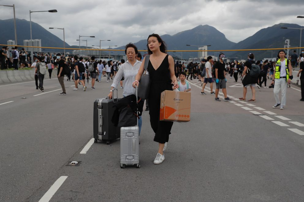 Passengers walk to airport as pro-democracy protestors blocked a road outside the airport in Hong Kong, Sunday, Sept.1, 2019. The operator of the express train to Hong Kong's airport has suspended service as pro-democracy protesters gathered there following a day of violent clashes with police. Protesters gathered at the airport after online calls to disrupt travel. (AP Photo/Kin Cheung)