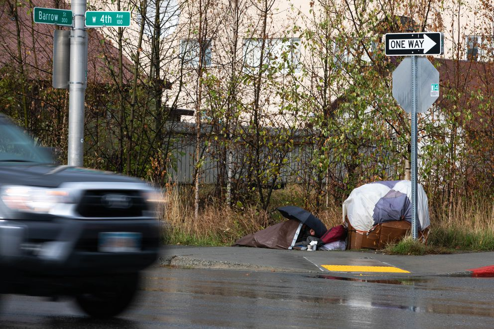 A person sleeps underneath a tarp in downtown Anchorage Wednesday, Sept 25, 2019. (Loren Holmes / ADN)