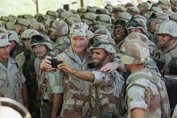 "FILE - In this Jan. 1, 1993, file photo, U.S. President George H.W. Bush holds a camera at arm's length for a selfie with Marines at Baidoa's airport in Baidoa, Somalia. Bush sent U.S. troops to help starving Somalis during his presidency and later teamed up with his one-time political rival, Bill Clinton, to raise money for victims of natural disasters. It was all part of Bush's vision for what he called a ""kinder, gentler nation."" Bush was a humanitarian and made volunteerism a hallmark of his presidency from 1989 to 1993. (AP Photo/John Moore, File)"