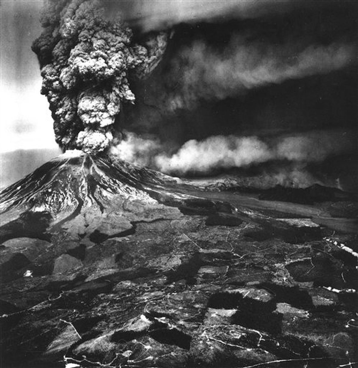 In this photo provided by the U.S. Geological Survey, is an aerial view of the eruption of Mount St. Helens volcano, Wash., May 18, 1980. White linear features are logging roads; dark patches are trees. (AP Photo/U.S. Geological Survey)
