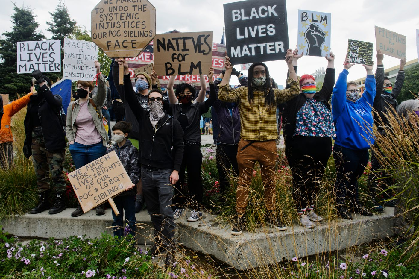 Several Black Lives Matter supporters holds signs and partially obscure a small counter-protest at Town Square. (Marc Lester / ADN)