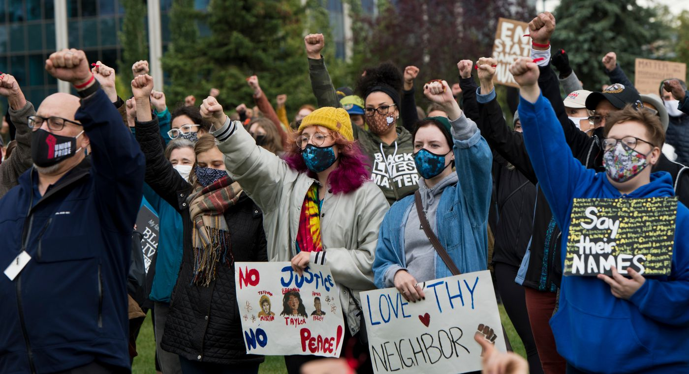 The crowd raises a fist together at the conclusion of the March on Alaska Monday. (Marc Lester / ADN)