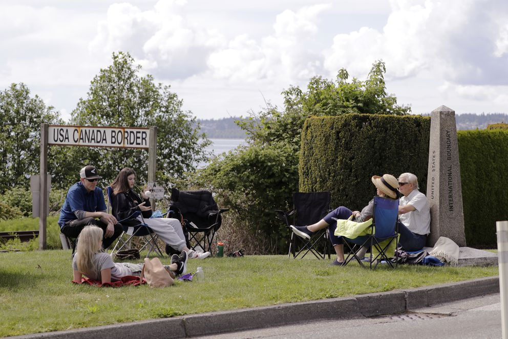 In this photo taken May 17, 2020, de Rham family members from the U.S. and Canada visit at the border between the countries in Peace Arch Park, in Blaine, Wash. (AP Photo/Elaine Thompson)