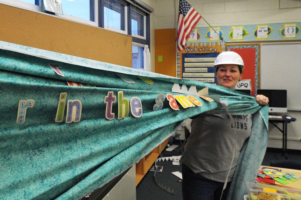 Special Education teacher assistant Rachel Williamson takes down a bulletin board at the earthquake-damaged Eagle River Elementary on Thursday. (Bill Roth / ADN)