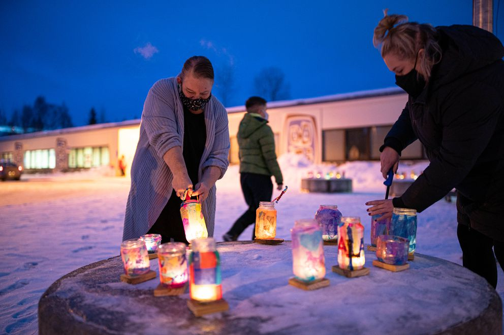 Music teacher Amy Spence, left, lights lanterns on the first day of in-person learning Wednesday, Jan. 20, 2021 at Tudor Elementary School. The student-decorated lanterns are a tradition at the school, and normally would be arranged along a walkway greeting students returning from winter break. (Loren Holmes / ADN)