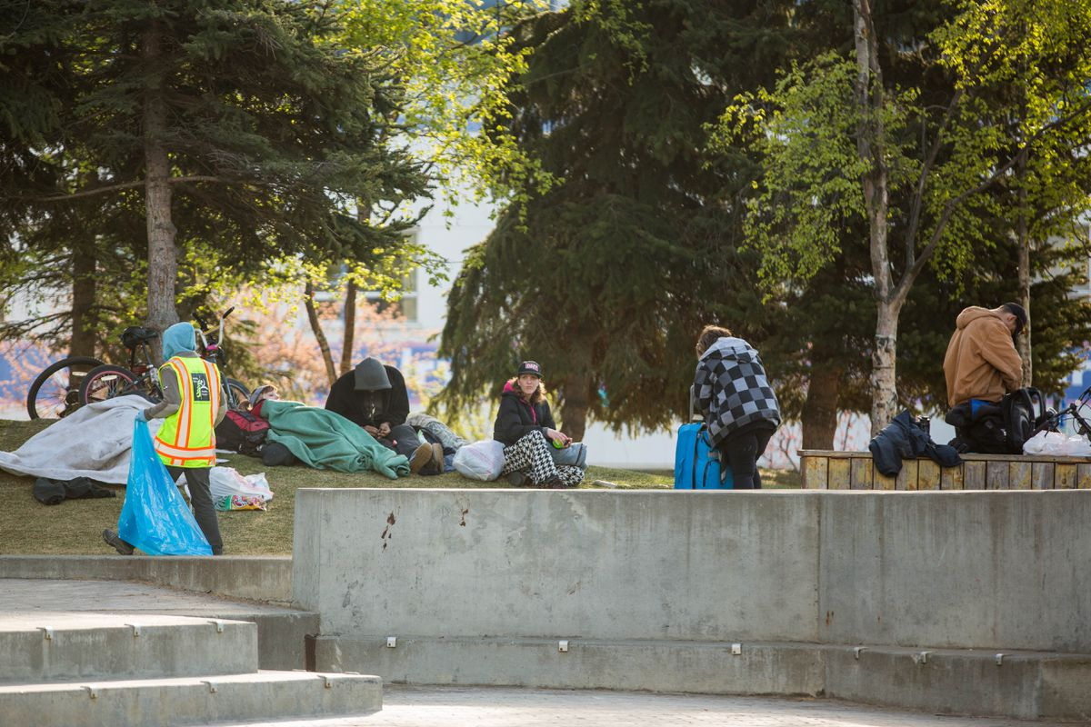 An Anchorage Parks employee picks up trash from around a group of homeless people in Town Square Park early Friday morning, May 6, 2016. A recent email from Anchorage Downtown Partnership director Jamie Boring that proposes privatizing downtown parks has many activists upset. (Loren Holmes / Alaska Dispatch News)