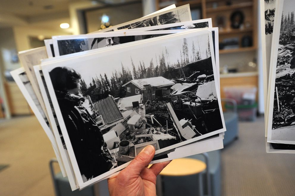 Anne Thomas Donaghy holds a photograph of her mother, Tay Thomas, and their Turnagain Heights home that was damaged during the 1964 Good Friday earthquake while sharing her experiences with residents at the Thomas Center on Dec. 5, 2018. (Bill Roth / ADN)