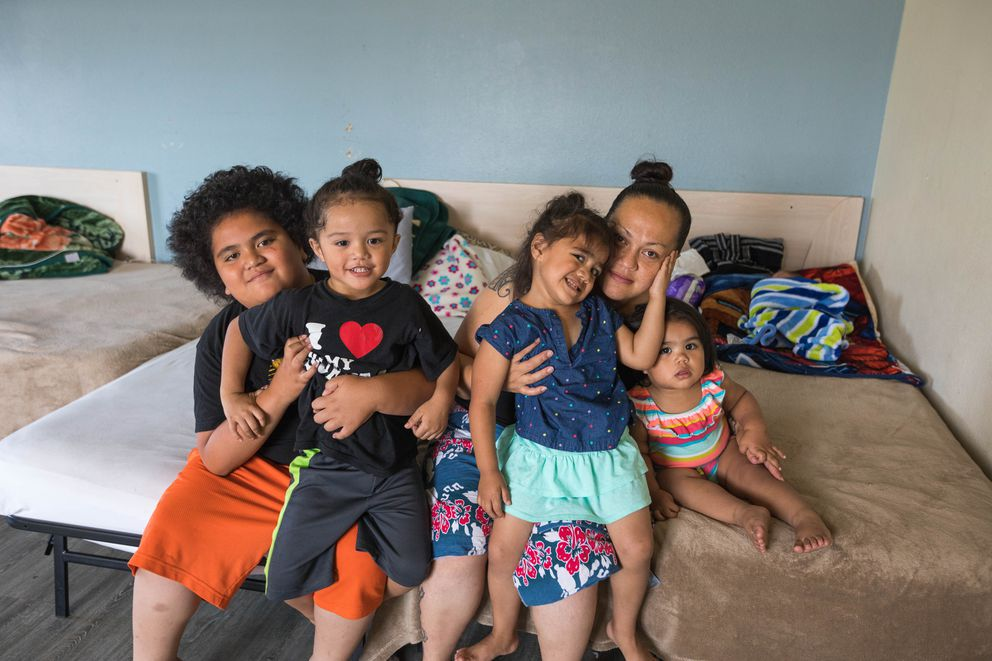Carrie Kelekolio, with five of her six children, in a studio apartment she rents with her husband at Safe Harbor, a transitional housing facility in Muldoon that will cease operations if Governor Mike Dunleavy's budget vetoes stand. From left is KJ Tuu, 9, Canaan Tuu, 4, Tina Tuu, 3, Kelekolio, Izzabelle Tuu, 1, and sleeping behind is Dallas Tuu, 1 week old. (Loren Holmes / ADN)