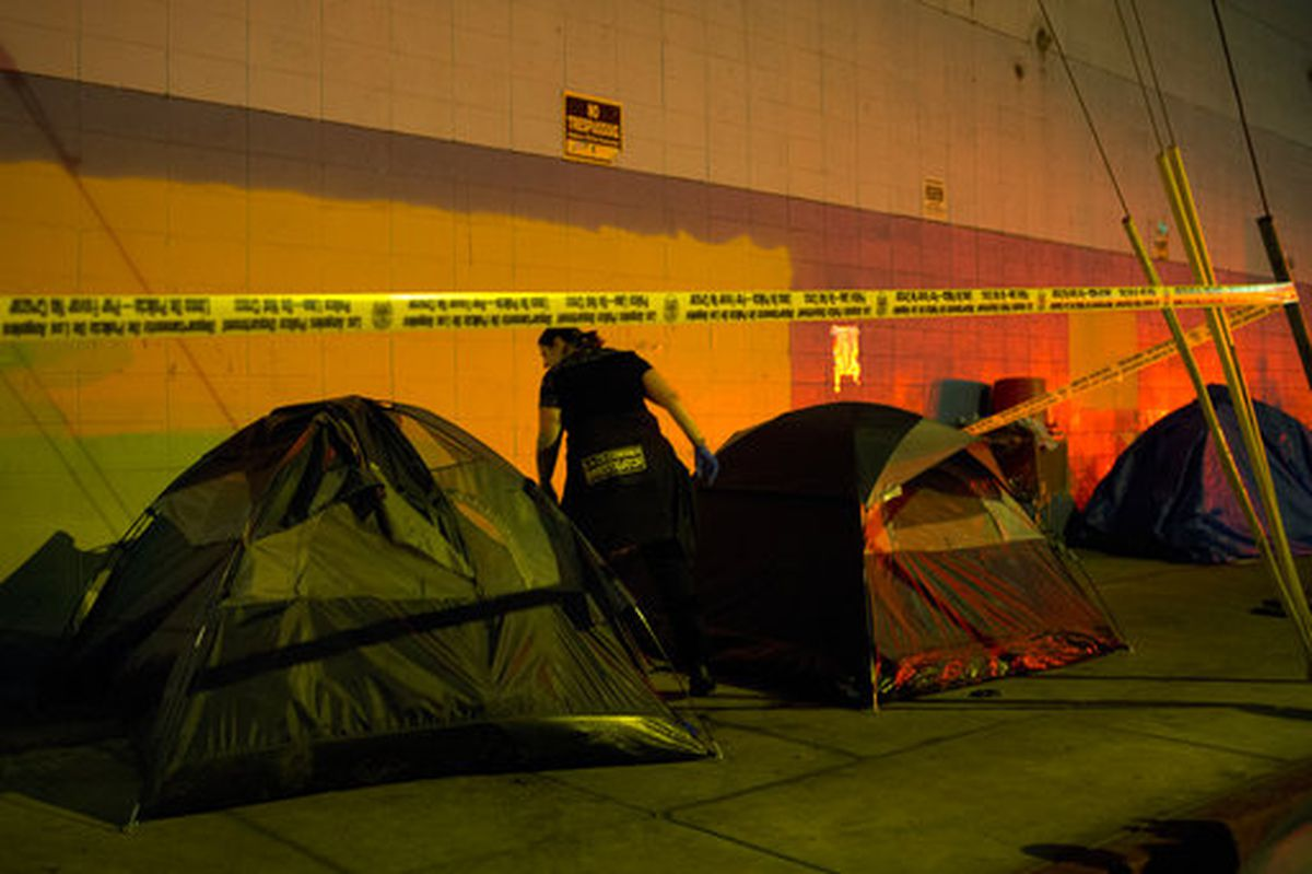 Los Angeles County investigator Kelli Blanchard looks around a tent Sept. 11, 2017, in the Skid Row area of downtown Los Angeles. (AP Photo/Jae C. Hong)