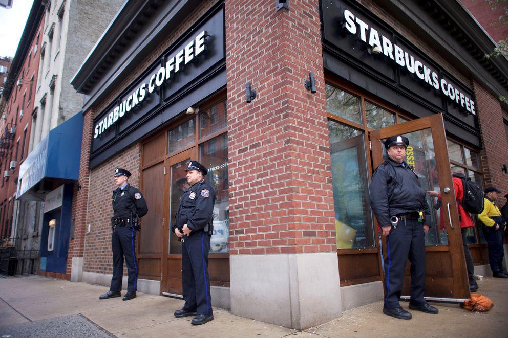 Police monitor activity as protestors demonstrate Monday inside a Center City Starbucks, where two black men were arrested, in Philadelphia. REUTERS/Mark Makela