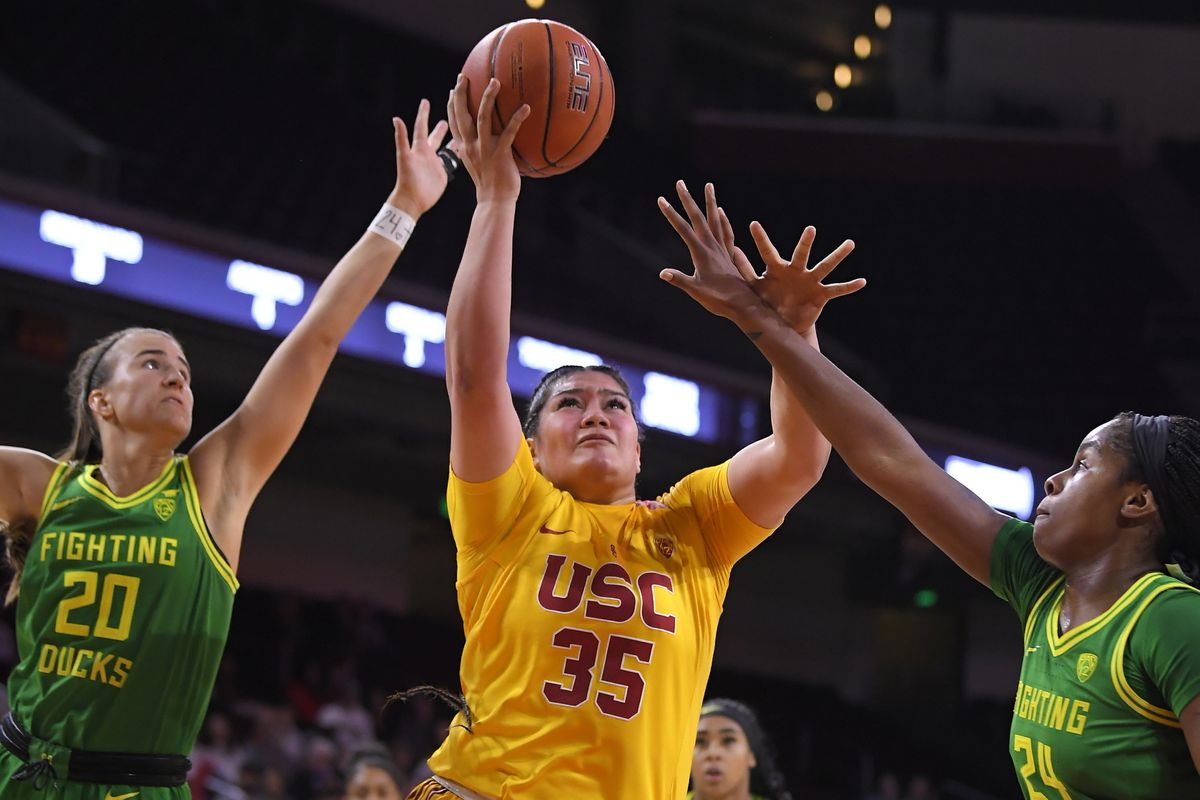 Southern California forward Alissa Pili, center, shoots while being defended by Oregon All-Americans Sabrina Ionescu, left, and Ruthy Hebard in a game last sesaon. (AP Photo/Mark J. Terrill)