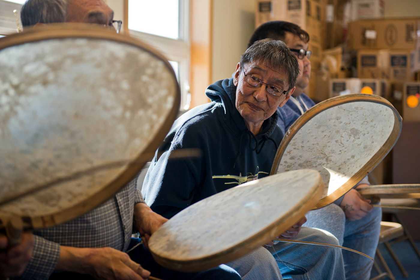 George Noongwook drums with other men at an event in the Native Village of Savoonga building on April 20. The drums are made with the stomach of walrus. (Marc Lester / Alaska Dispatch News)
