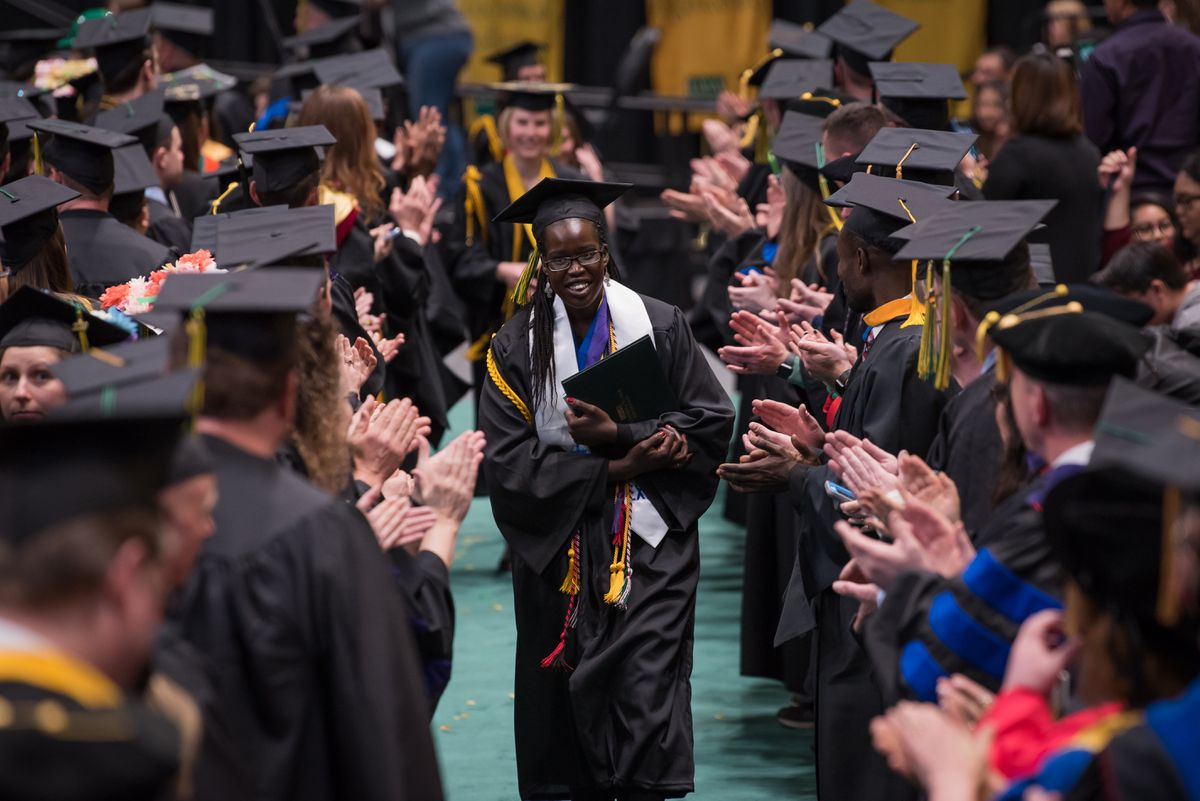Honors College grad Nyabony Gat, B.S. Health Sciences, is applauded by faculty as she and other grads leave the arena after UAA's 2019 Spring Commencement at the Alaska Airlines Center. (Photo by James Evans / UAA)