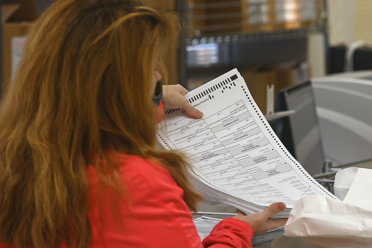 Election officials scan ballots during absentee partial counts at the Division of Elections Region II office in Anchorage on Tuesday, Nov. 17, 2020. (Bill Roth / ADN)