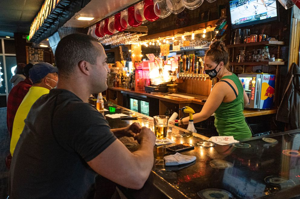David Sells watches a hockey game while bartender Sydney Hawk cleans bottles on Saturday at The Blue Fox. (Loren Holmes / ADN)