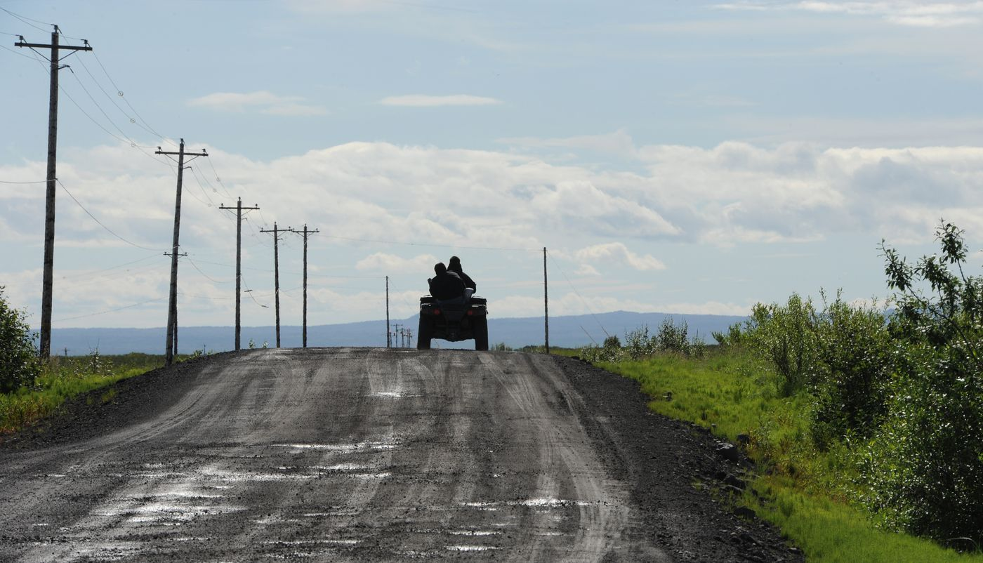 People travel on a four wheeler towards St. Michael on the gravel road that connects Stebbins and St. Michael, June 27, 2019. (Bill Roth / ADN)