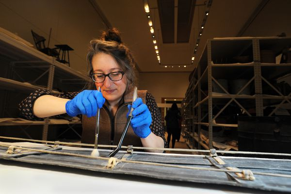 Private conservator Nicole Peters of Skagway uses a goat-hair brush and a low-suction vacuum to remove surface dust from a baleen sled while working in a former first-floor gallery space that now houses the conservation lab on Friday, March 31, 2017, at the Anchorage Museum at Rasmuson Center. (Erik Hill / Alaska Dispatch News)