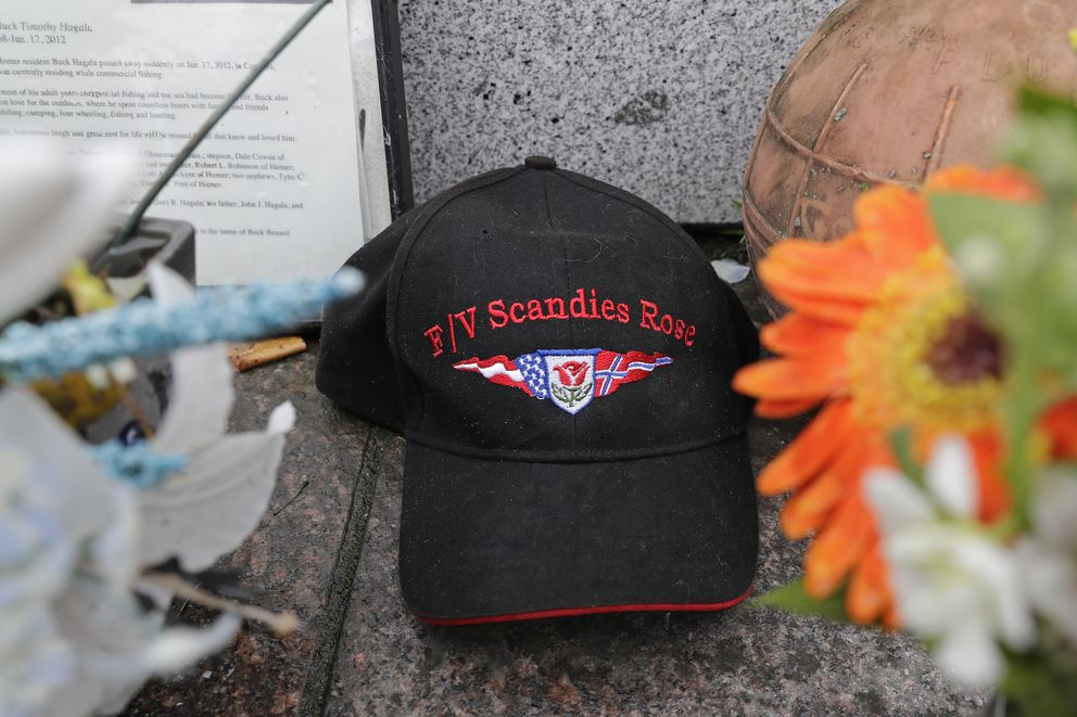 A ball cap with the name of the crab fishing boat Scandies Rose rests at the Seattle Fishermen's Memorial, Thursday, Jan. 2, 2020, in Seattle. The search for five crew members of the Scandies Rose in Alaska has been suspended, the U.S. Coast Guard said after two other crew members of the vessel were rescued after the 130-foot crab fishing boat from Dutch Harbor, Alaska, sank on New Year's Eve. (AP Photo/Ted S. Warren)