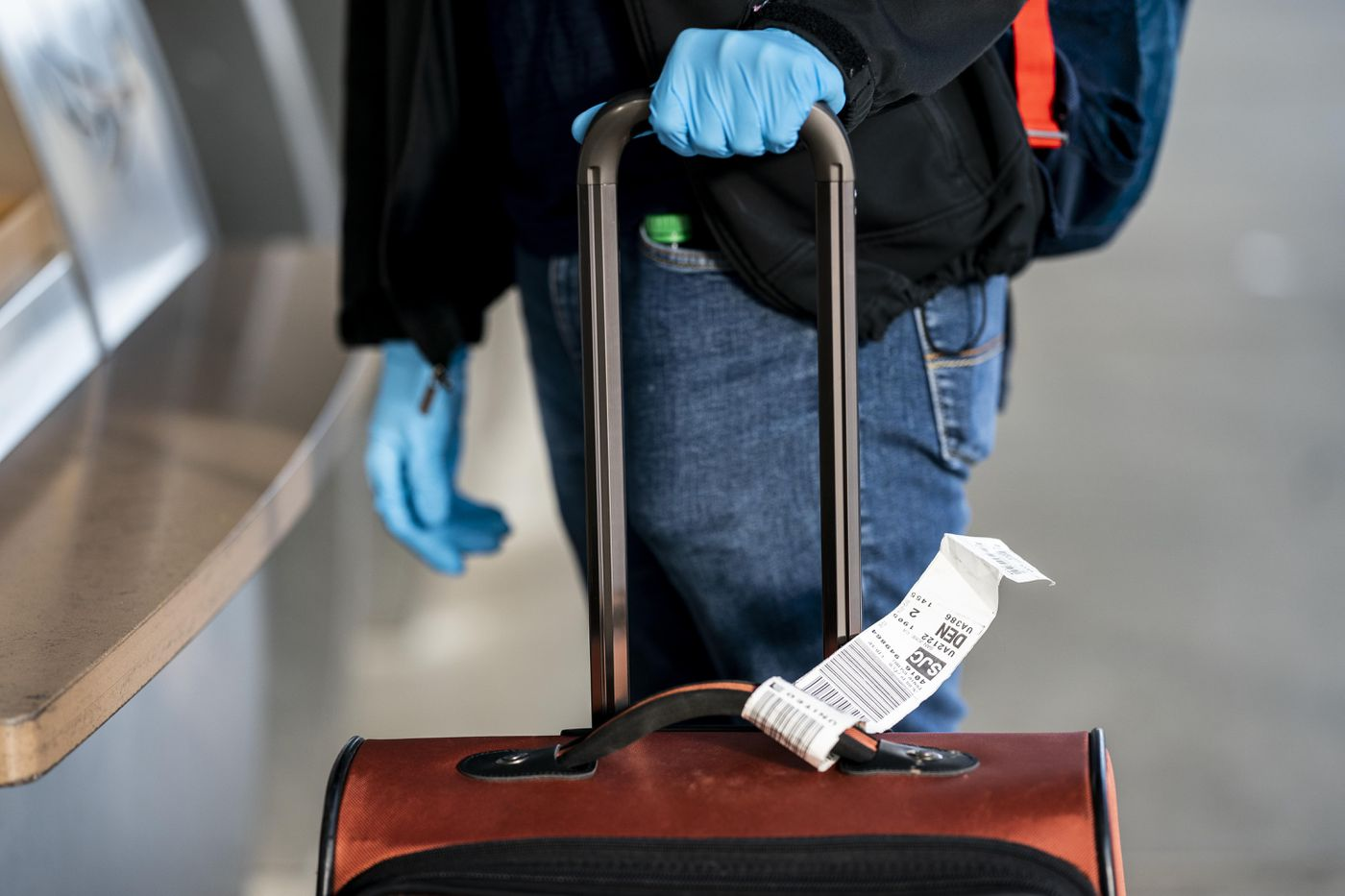 A traveler arrives with protective gloves to a quiet Norman Y. Mineta San Jose International Airport on March 20. Washington Post photo by Melina Mara
