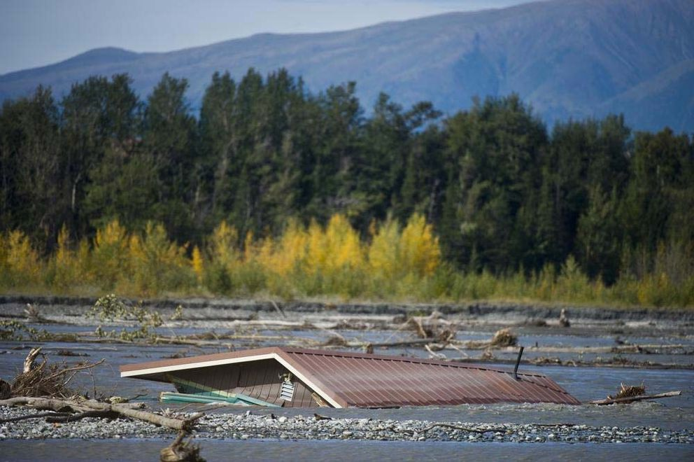 Wreckage of a cabin is partially submerged in the Matanuska River near the Butte on Wednesday, August 29, 2012. Christopher Wenner and his wife, Daina Mirsch-Wenner, own the house, which went into the river after erosion peeled away some of his land. They were using it as a rental property and live in a house behind it that they fear will soon be in the river too.